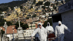 Des employés des pompes funèbres transportent le cercueil d'une personne décédée du coronavirus à Rio de Janeiro le 18 mai 2020. Le Brésil est particulièrement touché par l'épidémie.