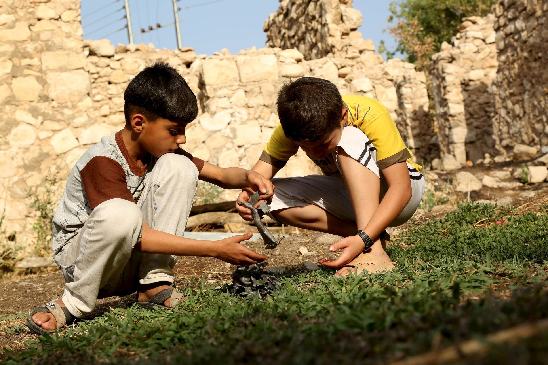 Niños juegan con un fragmento de bomba, lanzada por un avión militar turco en el norte de Irak.
