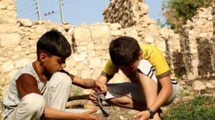 Deux enfants tiennent un morceau de débris de bombe lâché par l'aviation turque sur le village d'Amadiya en Irak du nord.