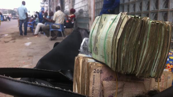 Des liasses de billets de francs congolais sur le sac d'une femme, à Kinshasa, en juillet 2016.