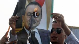 Wani mai adawa da Hosni Mubarak yana kone hoton shugaban