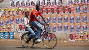 Un couple de jeunes Kenyans roule à vélo devant les affiches de campagne des différents candidats à la présidentielle, le 3 mars à Nairobi.