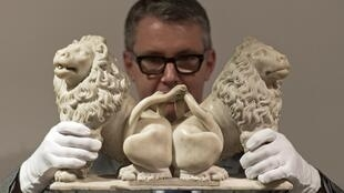 An employee poses for a photograph with a re-discovered sculpture of two carved marble lions, by French artist Andre Beauneveu, commissioned by French King Charles V, at Christie's auction house in London on February 20, 2017.