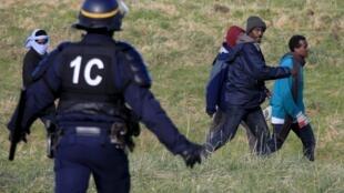Французский полицейский и мигранты недалеко от Кале, 21 января 2016 г.