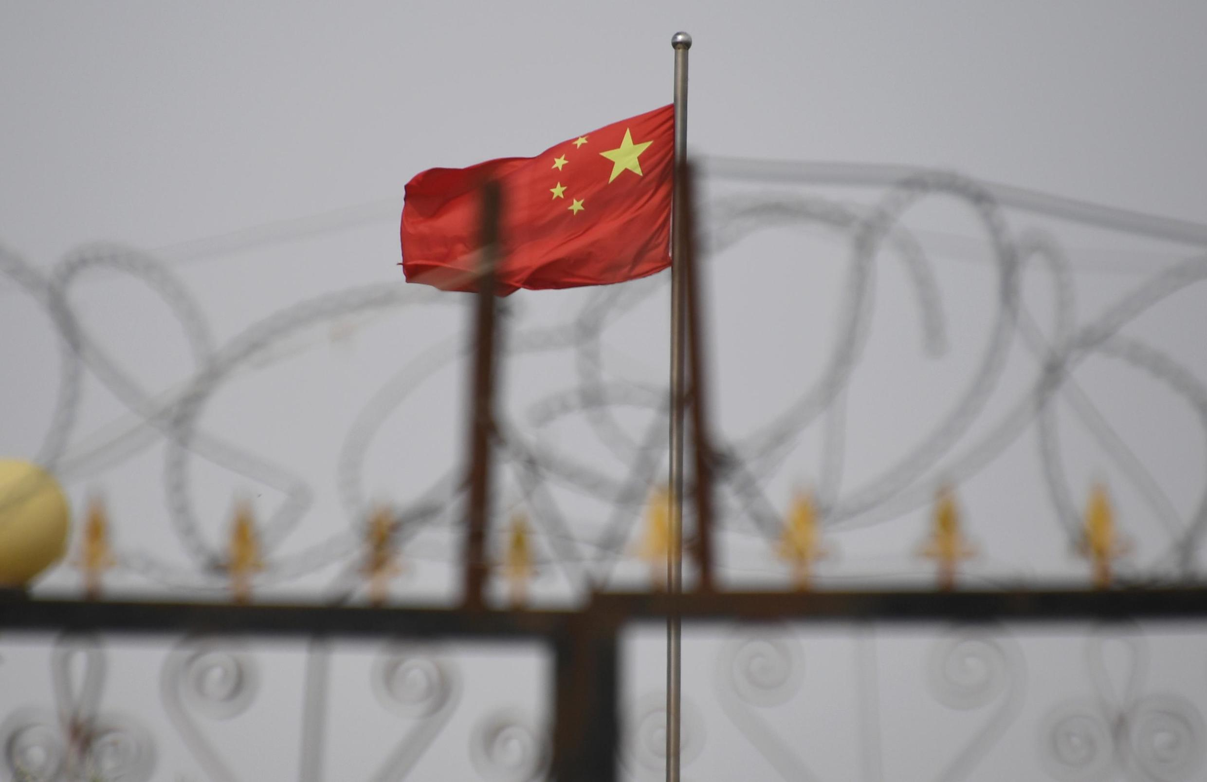 This photo taken on June 4, 2019 shows the Chinese flag behind razor wire at a housing compound in Yangisar, south of Kashgar, in China's western Xinjiang region.