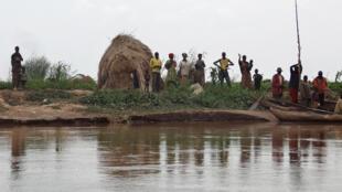Des habitants se tiennent sur les bords de la rivière Kagera où plusieurs corps ont été retrouvés.