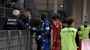 Amiens' French defender Prince Desir Gouano (L) approaches to see supporters he reported yelled racists insults at him as the match is interrupted due to the incident during the French L1 football match Dijon (DFCO) vs Amiens (SCO) on April 12, 2019.
