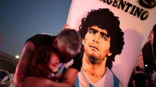 Supporters pleurant devant un drapeau à la gloire de la star argentine Diego Maradona, morte en novembre 2020.