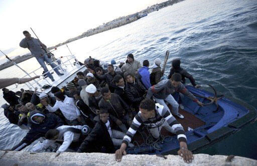 Une embarcation avec à son bord des migrants originaires d'Afrique du Nord entre dans le port italien de Lampedusa le 12 avril 2011.
