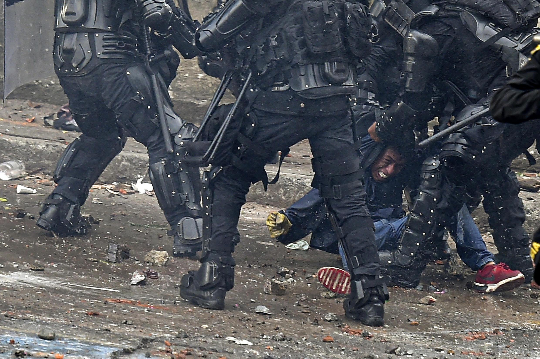 Des policiers colombiens frappant un manifestant à Cali le 10 mai 2021.