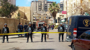 Egyptian riot police cordoning off the street at the site of a bomb attack in the northern port city of Alexandria, which hit a convoy of the city's security chief, on March 24, 2018.