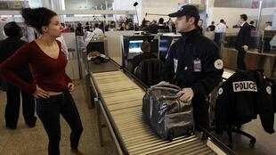 A French policeman checks a passenger at a security point in a terminal at the Charles-de-Gaulle airport in Roissy,