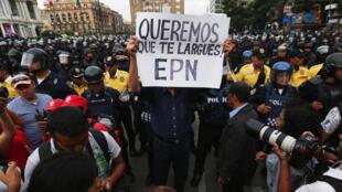 Un manifestante sostiene un cartel pidiendo la renuncia del presidente mexicano, el 15 de septiembre de 2016 en el centro de la ciudad de México.