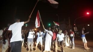 Al'ummar Sudan a dandalinsu na zanga-zanga kan neman gwamnati ta haramta Jam'iyyar tsohon shugaban kasar Omar Hassan al-Bashir.