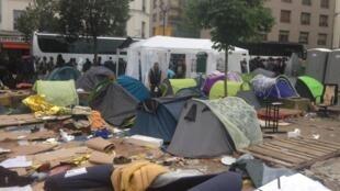 Refugiados deixam acampamento e embarcam em ônibus da prefeitura.