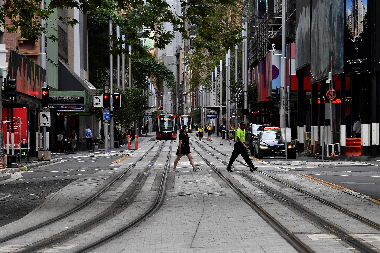 Pessoas atravessam uma rua tranquila no centro de Sydney, 25 de Março de 2020