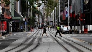 Pessoas atravessam uma rua tranquila no centro de Sydney, 25 de Março de 2020, enquanto as pessoas ficam longe devido às restrições para impedir a propagação da pandemia mundial.