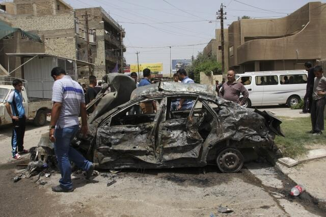 Residents gather at the site of a car bomb attack in Baghdad, 30 May, 2013
