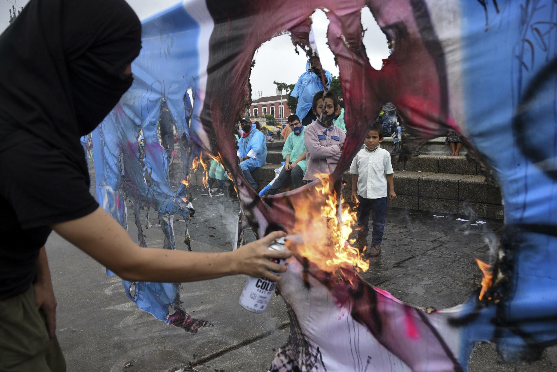 Un manifestante quema una pancarta con una imagen de la fiscal general de Guatemala, Consuelo Porras, durante una protesta que exige la renuncia del presidente guatemalteco Alejandro Giammattei y de Porras, el 29 de julio de 2021 en Ciudad de Guatemala
