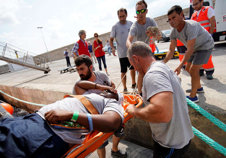 Des membres de l'ONG Proactiva Open Arms débarquent une migrante au port de Palma de Majorque, le 21 juillet 2018.