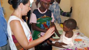 Au Niger, une infirmière de MSF et une infirmière locale examinent une petite fille dans une case de santé (école de santé).