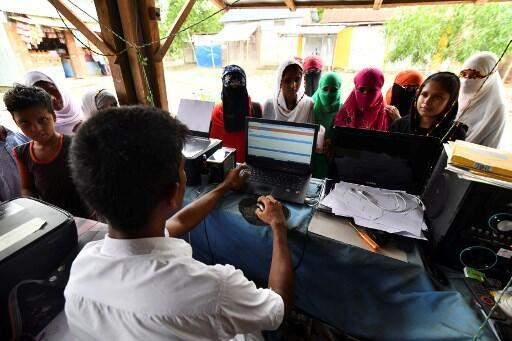 People check their names on the final list of the National Register of Citizens at a roadside shop in Pavakati village of Morigoan district, some 70 killometres from Guwahati, the capital city of India's north-eastern state of Assam.