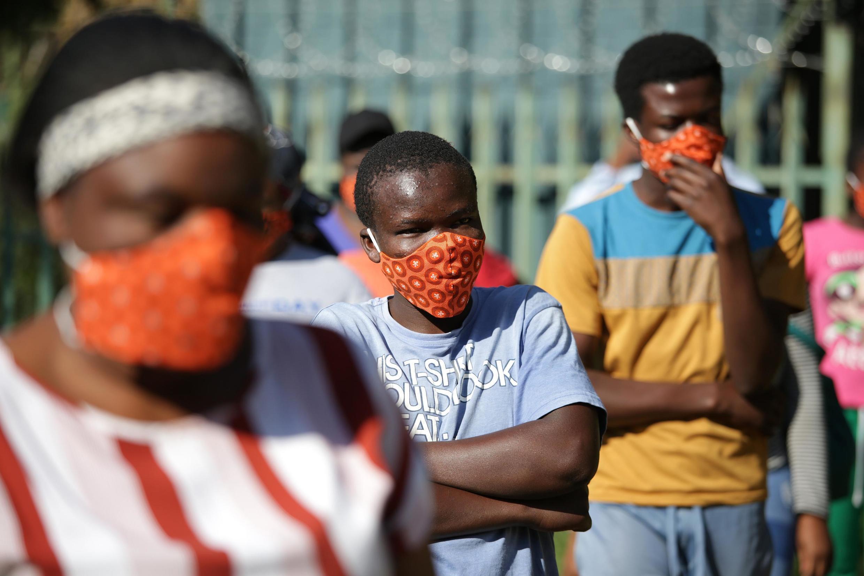 Des jeunes sud-africains portent des masques alors qu'ils attendent des colis de nourriture du capitaine de l'équipe nationale de rugby sud-africaine Siya Kolisi et des membres de la Fondation Nelson Mandela au nord de de Johannesburg, le 25 avril 2020.
