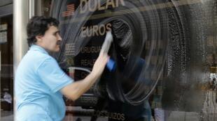 Homem limpa fachada de casa de câmbio em Buenos Aires, nesta segunda-feira.