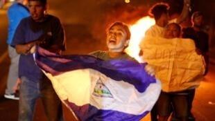 Um manifestante segura uma bandeira da Nicarágua ao lado de uma barricada em chamas enquanto manifestantes participam de um protesto contra uma reforma controversa dos planos de pensão do Instituto Nacional de Seguro Social da Nicarágua (INSS) em Manágua,