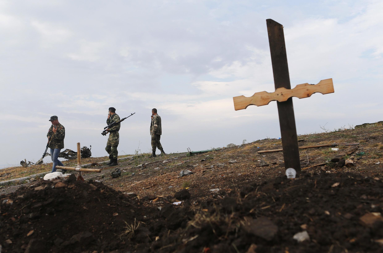 Soldados pró-russos enterram vítimas do conflito em Donetsk, reduto dos separatistas no leste da Ucrânia, nesta quinta-feira (28).