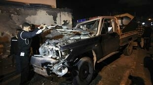 Police stand near a police car, which is destroyed after an explosion in front of a police station in Benghazi, 12 December