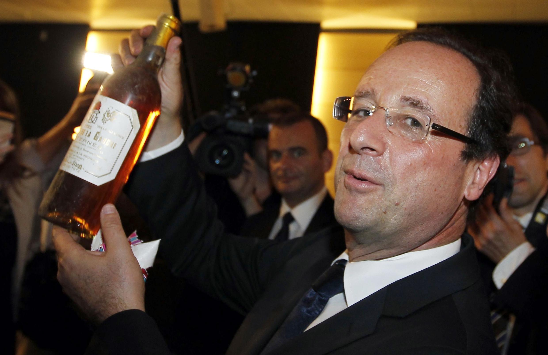 Франсуа Олланд с бутылкой вина, полученной в подарок во время посещения Генерального совета департамента Коррез в Тюле 11/05/2012