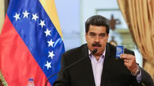 Nicolas Maduro brandit une copie de la Constitution du Venezuela devant les membres du corps diplomatique, lundi 28 janvier 2019, au palais de Miraflores à Caracas.