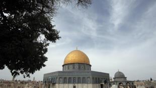Palestinos andam na frente da mesquita Al-Aqsa, em Jerusalem, antes da oração da sexta-feira.  23 de outubro 2015.