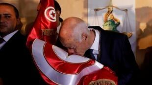 Kaïs Saied besa la bandera tunecina tras el anuncio de su victoria, el 13 de octubre de 2019.