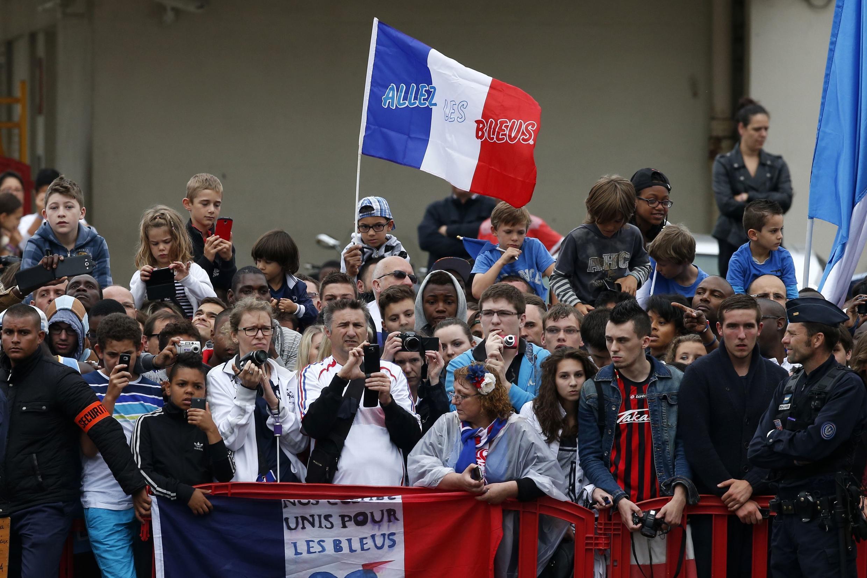 Torcedores aguardam chegada da seleção francesa, após derrota contra a Alemanha.