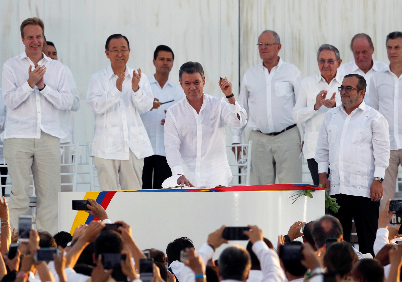 Le président colombien Juan Manuel Santos (C), le stylo-bille à la main, et le chef des FARC (D) lors de la signature de l'accord de paix, le 26 septembre 2016 à Carthagène. (Image d'illustration)