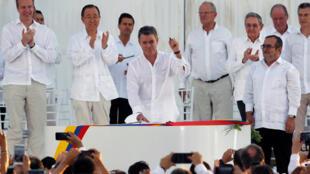 Le président colombien Juan Manuel Santos (C), le stylo-balle à la main, et le chef des FARC (D) lors de la signature de l'accord de paix, le 26 septembre 2016 à Carthagène.