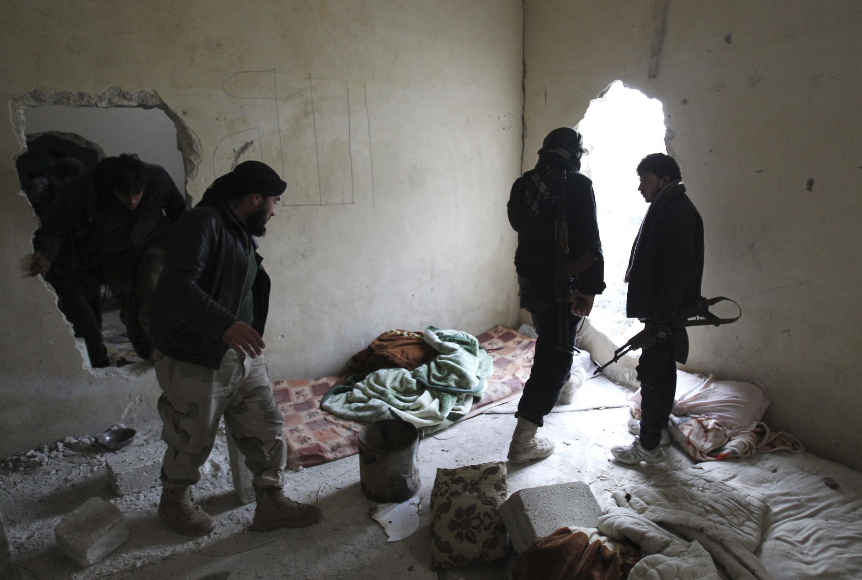 Wasu Mayakan Kungiyar al Nusra suna rike da makamai a wani gida da suke buya a yankin Aleppo a Syria
