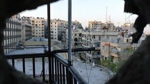 A rebel fighter looks out onto Aleppo's Izaa district from an empty apartment.