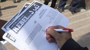 Un homme signe la pétition «Tamarod» sur la place Tahrir, au Caire, le 16 mai 2013.