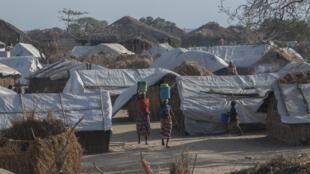 Dos mujeres caminan por el campamento de desplazados en Metuge, el 9 de diciembre de 2020, donde ahora se albergan más de 16.000 personas de la zona norte de Cabo Delgado, en Mozambique