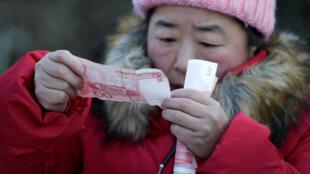 图为一名中国妇女在检测手中人民币百元大钞