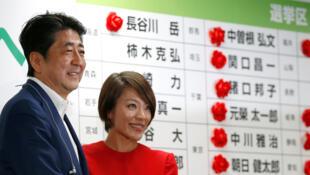 Le Premier ministre japonais, Shinzo Abe (G) serrant la main d'Eriko Imai, candidate pour son parti à l'élection sénatoriale du 10 juillet 2016, à Tokyo.