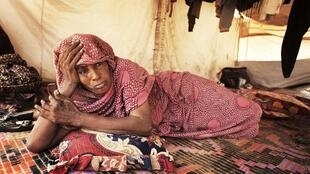 A woman lies on the floor of her home, a tent provided by the UNHCR, in Mbera refugee camp, Mauritania