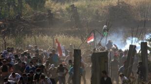 Des manifestants s'enfuient après un lâcher de gaz lacrymogènes par les soldats israéliens sur le plateau du Golan, le 5 juin 2011.