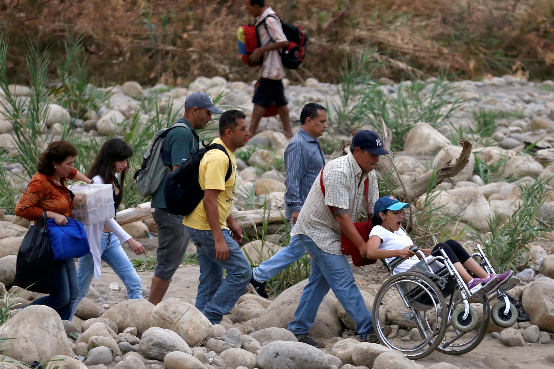 Gente cruzando el río Táchira en la frontera de Colombia con Venezuela, en las afueras de Cúcuta, Colombia, el 13 de abril 2019.