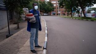 Un vendeur de journaux rwandais dans les rues vides de Kigali, le 22 mars 2020.