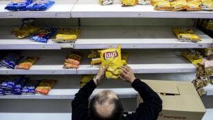 Un empleado de supermercado coloca un paquete de comida con las nuevas etiquetas conformes a la nueva normativa, el 20 de junio de 2016 en Santiago.