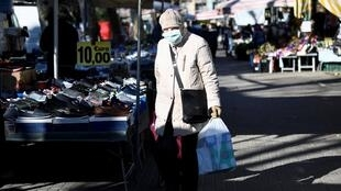 En pleine période de confinement, une personnage âgée et masquée s'autorise une sortie sur un marché de Milan, en Lombardie, le 11 mars 2020.